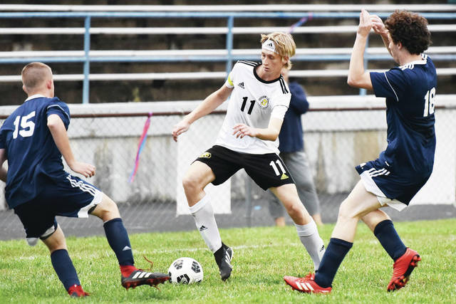 Sidney's Michael Koester looks to get around Piqua's Costas Elliott, left, and Kyle Pierre during a Miami Valley League crossover game on Tuesday at Wertz Stadium in Piqua. Koester scored two goals.