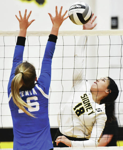 Sidney sophomore outside hitter Aliyah Taborn sends the ball over as Xenia's Paige Shouse tries to block during a Miami Valley League Valley Division match on Wednesday in Sidney. Taborn made eight kills.