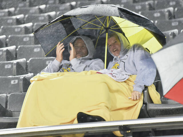 Mark and Laura Gibson, both of Sidney, didn't let windblown rain stop them from watching their twin sons Will and Joe Boehm, play an eighth-grade football game against Fairborn at Sidney Memorial Stadium on Wednesday, Sept. 22. According to the couple most of the parents were watching the game from the safety of the press box.