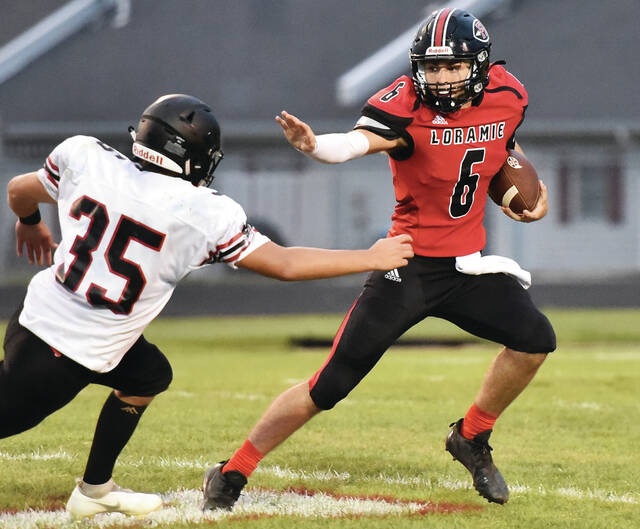 Fort Loramie's Caleb Maurer runs while trying to avoid Covington's Jensen Wagoner during a game on Friday at Redskin Stadium. Maurer threw for 224 yards and three touchdowns.