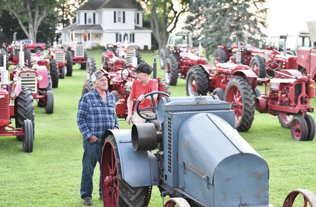 Ernie Hageman, left, with his grandson, Kyle Wright, 13, both of Green Township, on Monday, Sept. 6. Kyle is sitting on one of Hageman's 48 antique tractors. Hageman started collecting antique tractors six years ago. His oldest tractor is a 1919 Titan. Hageman had all his tractors taken out of storage because they need to run occasionally or they can sustain damage from sitting idle for too long. Hageman recently expanded his storage barn when he ran out of space for his tractors. He is mostly done purchasing antique tractors but there are a few choice tractors he would still like to buy. Kyle has gotten into the collecting business with a tractor Hageman bought at auction and gave to Kyle. The tractor was originally owned by Kyle's great great grandpa Martin Cromes. Kyle is the son of Eric and Jill Wright.