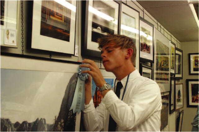 """Paul Hinds, 17, son of Joe and Kazy Hinds, hangs his honorable mention ribbon on his photograph, """"Yosemite Valley."""" Hinds participated in the 29th Annual Piqua Fine Art Exhibit for the first time this year, and is hoping to pursue photography and videography into college next year at the University of Oregon."""