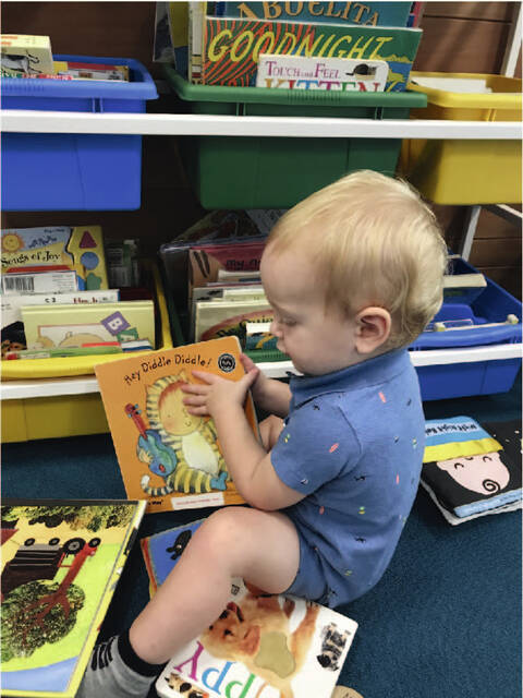 Amos Unterbrink, 1, explores the book collection in the Early Literacy Center at the Amos Memorial Public Library. The Early Literacy Center for ages 0 to 5 and a caregiver is open during regular library hours in Sidney.