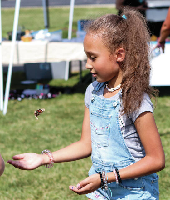 Taya Hendrickson, 7, of Botkins, lets a butterfly go during Samaritan Works Walk for Recovery on Saturday Sept. 18. Taya is the daughter of Danae Hendrickson and Mitchell Marshall.