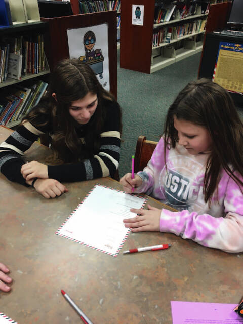 Big Buddy mentor, Madison Warner of Ansonia helps her little buddy, Grace Graf, daughter of Benjamin and Emily Graf, of Ansonia, with peace works curriculum.