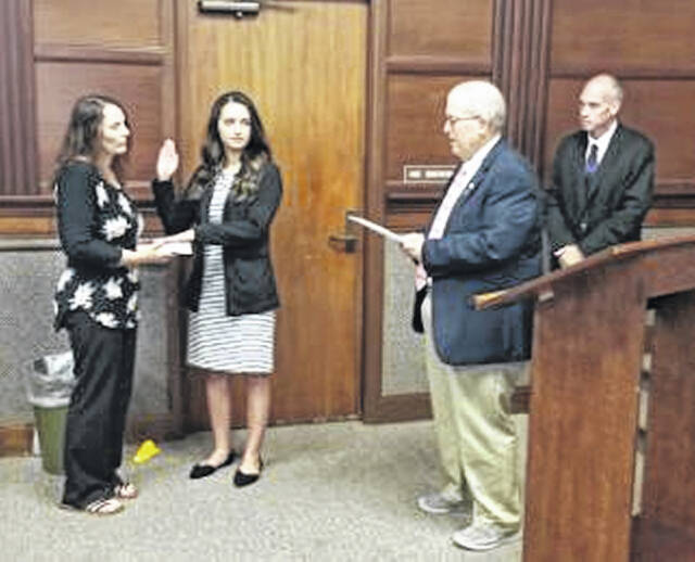 Sidney's newest police officer, Kiarra Ibarra, center, is sworn-in by City Manager Mark Cundiff, second from right, and Police Chief Will Balling, far right, with her mother Amy Taylor by her side, holding The Bible.