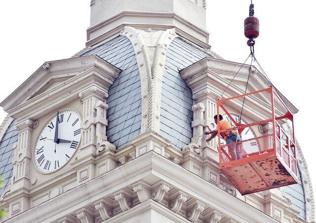 Suspended by a crane, Joe Celestino, of Bucyrus, patches holes in the Shelby County Courthouse's clock tower on Tuesday, Aug. 31. A worker inside the tower would tell Celestino where he saw light coming through the walls and try to guide him toward the holes. The patching was part of routine maintenance on the building. Celestino expects to be done by Thursday, Sept. 2. Celestino works for Midwest Maintenance Inc.
