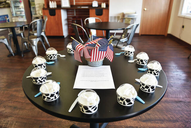 """K & J's Ice Cream has set a table in memory of the 13 U.S. service members killed during a suicide attack at the Hamid Karzai International Airport in Kabul, Afghanistan. The U.S. service members were working to evacuate people as the U.S. ended its 20 year war in Afghanistan. Eleven Marines, one Navy corpsman and one soldier were killed. A sheet of paper on the table lists the names of each soldier that died. It ends with the Bible quote """"Greater love hath no man than this, that a man lay down his life for his friends"""" John 15:13."""