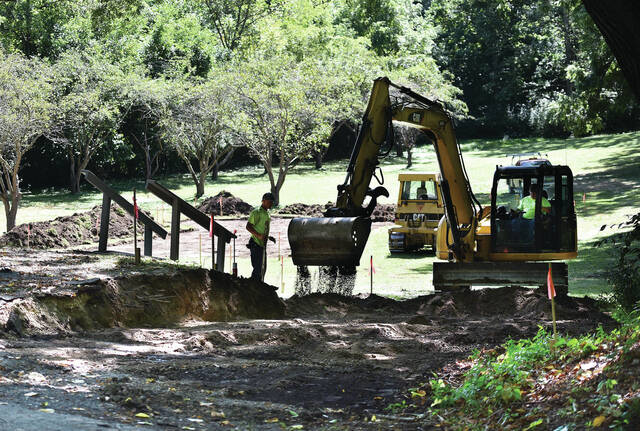 Logan McGee, left, of Versailles, watches as Dusty Furrow, of Covington, moves dirt where a driveway will be installed leading down to a parking lot in Aschenbach Grove on Thursday, Sept. 9. The parking lot will be for the gazebo that will be built among the trees in the grove. The gazebo is being donated by Albert Dickas, of Blacksburg, Va., in memory of his great-grandpa William Binkley, who was the editor of the The Sidney Journal from 1869 – 1905. Dickas grew up in Sidney. He used to play in Tawawa Park as a kid.