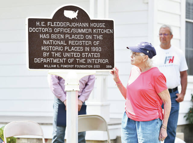 Beverly Fledderjohann, of New Knoxville, looks at the historical marker that she helped unveil at the New Knoxville Heritage Center on Saturday, Sept. 11.