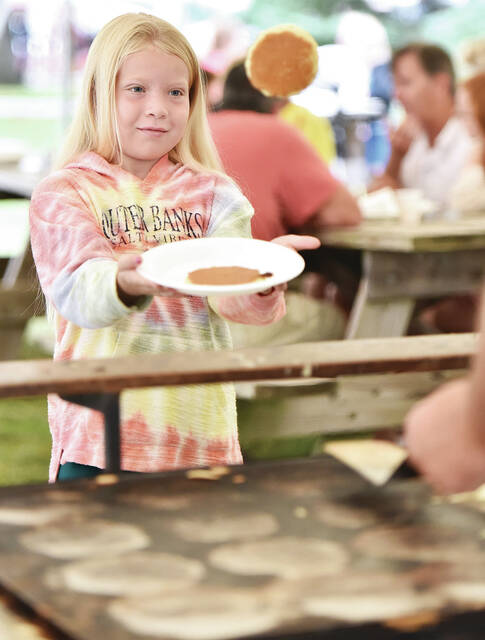 Torryn Schotte, 8, of Houston, daughter of Matthew and Brooke Schutte, catches a pancake flipped towards her at the Sidney Rotary Club's 17th annual Pancake Breakfast on Saturday, Sept. 11, on the northeast corner of the courthaquare.
