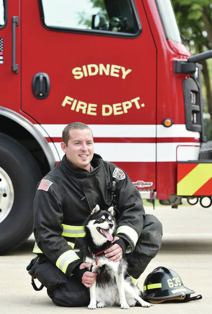 VanBuren Township firefighter Dakota Blair poses with Mika, a pomsky, owned by the family of Candace Alig, Jason Alig and Hope Alig, all of Botkins. Mika was one of 11 dogs and one cat that raised enough money to be included in the 2022 SCARF Top Pet Calendar. On Monday, Sept. 13, the pets were photographed for the calendar with local firefighters at the Sidney Fire Department.