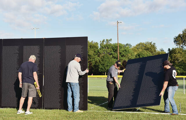Helping to assemble the traveling Vietnam Wall at Custenborder Field are, left to right, Vietnam Army Veteran Roger Bertke, of Fort Loramie, Vietnam Army Veteran Mark Schlagetter, of Sidney, Vietnam Army Veteran Bob Wyen, of McCartyville, and Brandon Ream, of St. Marys. The Wall was put-up at 8 a.m. on Thursday, Sept. 16.