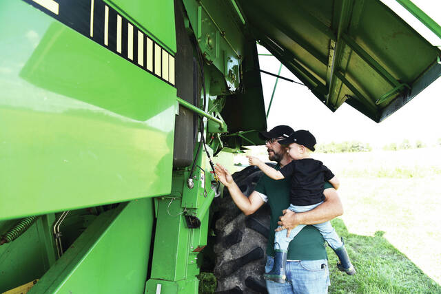 Farmer Jason Gibbs gives his son Aiden Gibbs, 2, both of Jackson Center, a lesson in safety around their combine near Maplewood on Friday, Sept. 17. Aiden is also the son of Shelby Gibbs.