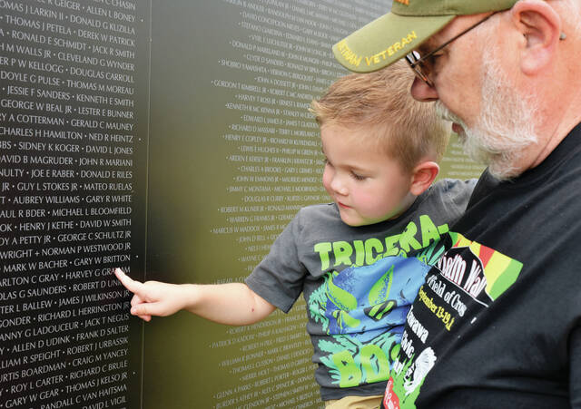 Steve Egbert, right, of Sidney, shows his 3 yr old Grandson, Britton Seiber, of Houston, the name of his Vietnam War squad leader, Gary Britton, who was killed in 1970 Vietnam while trying to rescue a fallen member of their company. When Britton was born 3 yrs ago Egbert's Son in law Matt and Egbert's daughter Diana asked if Steve would mind if they named their son after SSGT Gary Britton.