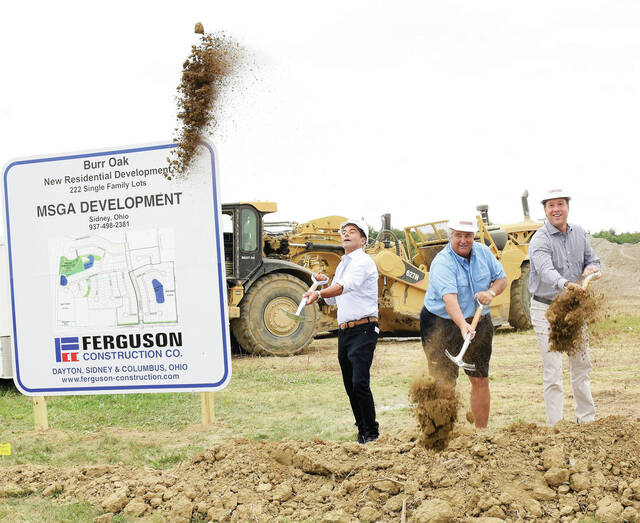 Phil Gilardi, Mick Given and Ben Scott throw dirt into the air as ground is broken on Monday, Sept. 21, for the new Burr Oak development at the intersection of Russell Road and Fourth Avenue. The project is part of MSGA Development. The subdivision will see the development of 222 single family lots in addition to multi-family residential and commercial areas which will be developed at a future date. Ryan Homes is in charge of the housing development. City and county officials were on hand for the groundbreaking ceremony.