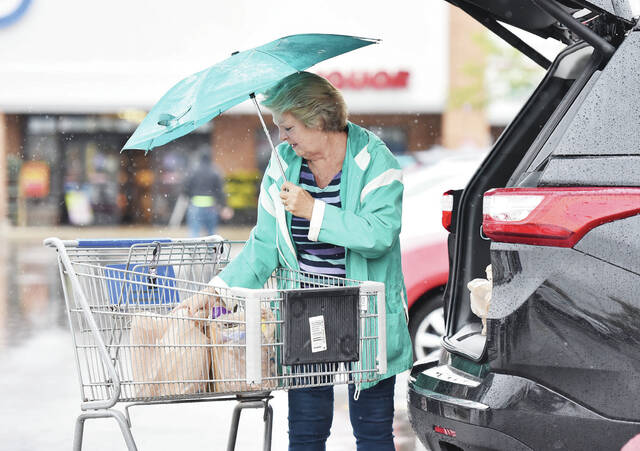 Kathy Fultz, of Sidney, performs a balancing act trying to hold an umbrella in one hand and load groceries into her SUV with the other in the rain in front of Kroger on Wednesday, Sept. 22.