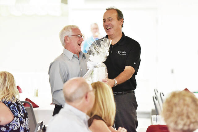 The current Ruese President Rudy Keister, right, hands a raffle prize to past Ruese President Mark Dunham, both of Sidney, during a Business After Hours event celebrating the 135th anniversary of Ruese Insurance Group. The event was held at the Oaks Club on Tuesday, Sept. 21. Food was served and there was a display of historical information about the company.