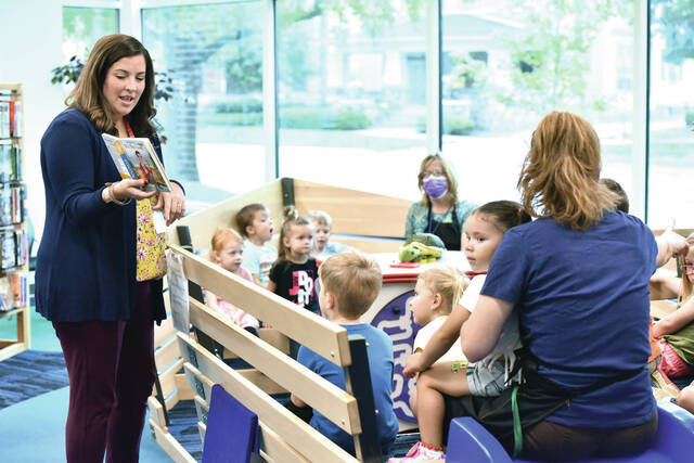 """Children's Outreach Coordinator April Orsborne, of Sidney, reads """"It's You I Like,"""" by Mr. Rodgers, to a group of kids at the Amos Memorial Public Library on Wednesday, Sept. 15. In-person story time was suspended through 2020 and into early 2021 due to Covid-19 but it has now returned."""