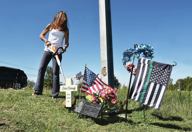 On Friday, Sept. 24, Kelly Knouff, of Anna, uses a weed trimmer to clear tall grass that had been obscuring the roadside memorial for her late husband Chris Knouff located on the County Road 25A and I-75 overpass. Knouff has cleaned up the memorial a minimum of three times a month for the last two years. She wants to bring awareness to how dangerous the overpass is. Knouff would like to see traffic lights built on the overpass like the other two Sidney overpasses with ramps. Chris was killed on July 23, 2019, when a woman on the County Road 25A overpass was turning left onto the I-75 south bound on ramp and turned directly into the path of Chris who was headed into Sidney on a motorcycle for work. While Kelly Knouff was cutting grass three cars went down the southbound I-75 on ramp then drove backwards back up the ramp when they saw the traffic jam caused by roadwork. Chris was an organ donor and 75 people benefited from his donations. Chris was a staff sergeant in the Ohio National Guard and served in Operation Desert Storm and Operation Iraqi Freedom.