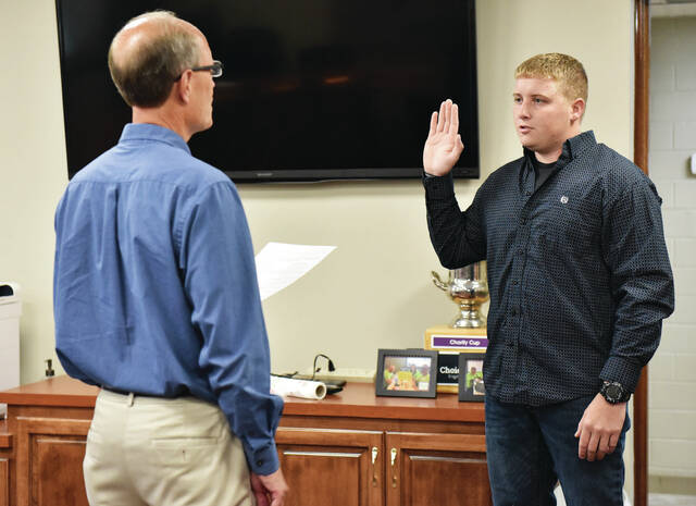 Fort Loramie Mayor Randy Ahlers, left, swears in part time police officer Cameron Keiser, of New Weston, on Friday, Sept. 24. The Village of Fort Loramie has also recently hired Brandon Johnson and Morgan Styles as part time police officers.