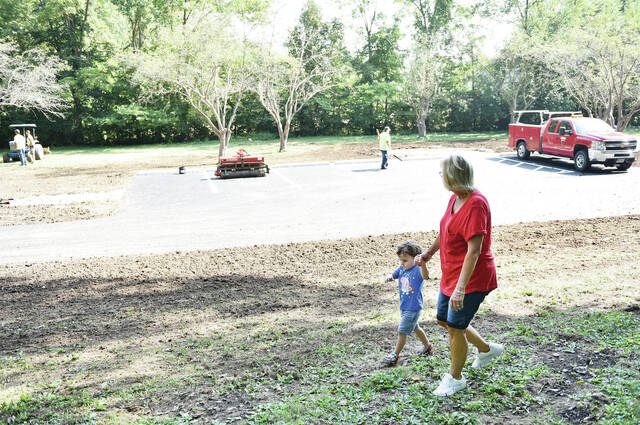 Evan Britt, left, 2, walks with his grandma, Kim Krempel, both of Sidney, pass the newly built parking lot in Aschenbach Grove in Tawawa Park on Tuesday, Sept. 28. Britt's mother, Emily Britt and his brother Elliott Britt, 4, also were walking with them to see Big Rock at the back of Aschenbach Grove. A gazebo will be built next to the parking lot. Evan and Elliott are also the sons of Eric Britt.