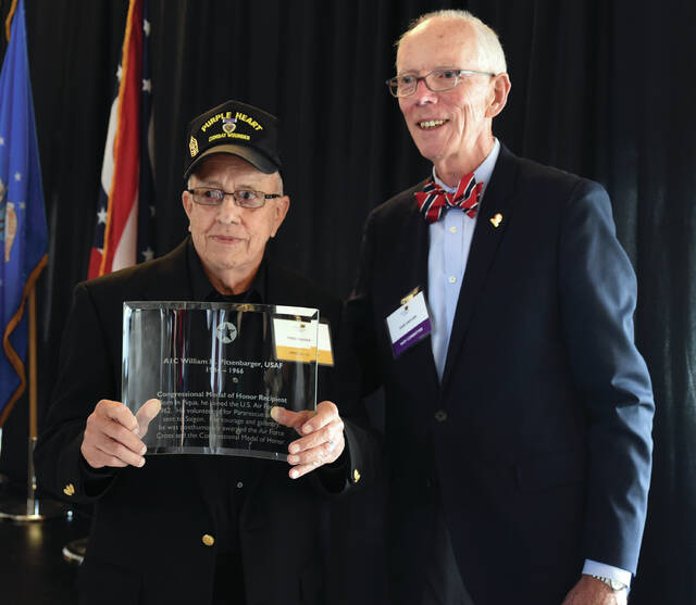 Charlie Company veteran Fred Navarro, of San Antonio, TX, accepts the 2020 Wright Dunbar Dayton Region Wall of Fame Award on behalf of Piqua native A1CWilliam H. Pitsenbarger, USAF, who earned the Medal of Honor for his actions in the Vietnam War, which saved the life of Navarro and other members of Charlie Company, 1st Infantry Division, U.S. Army, in April 1966. Handing the plaque to Navarro is Walk of Fame committee chairman Dan Sadlier.