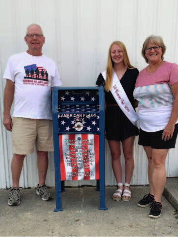 Aubrey Baker, 17, daughter of Jack and Annette Baker, stands next to her Retired Flag Drop Box she created as part of her project for the Fort Loramie Liberty Days Queen contest. On the left is Roger Bertke, Commander, Fort Loramie American Legion, Post 355, and on the right is Cindy Plas, President, Fort Loramie American Legion, Unit 355.