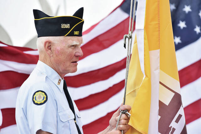 Minster American Legion Post 387 member Orville Borgert, of Sidney, prepares to raise the village of Minster flag at the opening ceremony for Minster Oktoberfest on Saturday, Oct. 2.