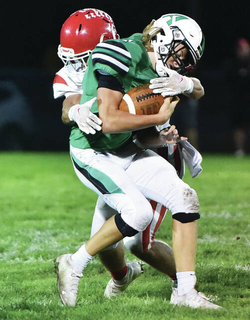 Anna's Zach Ambos is tackled by St. Henry's Jaden Lange during a Midwest Athletic Conference game on Friday at Booster Field. The Rockets dropped their fourth consecutive game with a 26-7 loss and fell to 3-5 overall.