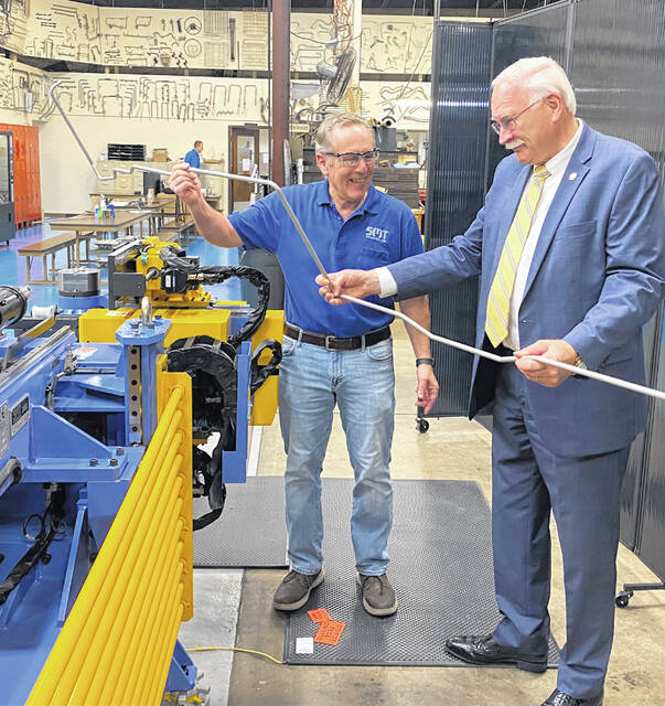 Sidney Mayor Mike Barhorst and SMT President Ron Duval examine a hydraulic line next to a machine SMT Industrial recently finished building for one of their customers that manufactures vehicular hydraulic lines.