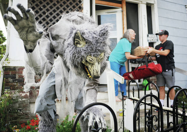 A werewolf stands menacingly in the yard of Diana McWilliam's, left, as she accepts some pizzas from delivery man Bryce Landrey, both of Sidney, on Thursday, Sept. 30. The werewolf is one of several large and realistic monster replicas that McWilliam's children have put up in their yard along Pike Street.