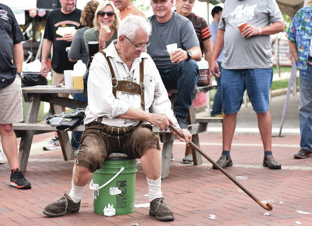 Don Richard Forquer, of Circleville, reaches for a piece of thrown candy with his cane at the Minster Oktoberfest Parade on Sunday, Oct. 4. Forquer tossed the candy to nearby kids after acquiring it.