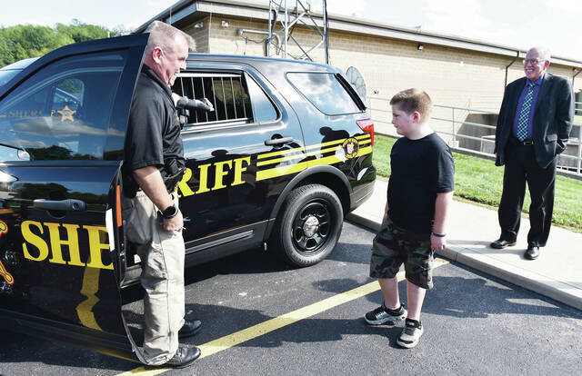 Shelby County Sheriff's Office Sgt. Ed Garrett, left to right, gives a tour of his cruiser to Zander Deubner, 9, of Sidney, as Shelby County Sheriff Jim Frye watches in the Shelby County Sheriff's Office parking lot on Tuesday, Sept. 28. Zander had recently delivered pizzas to the Shelby County Sheriff's Office and in return he was given a tour. Zander is the son of Jill and Jennifer Deubner.