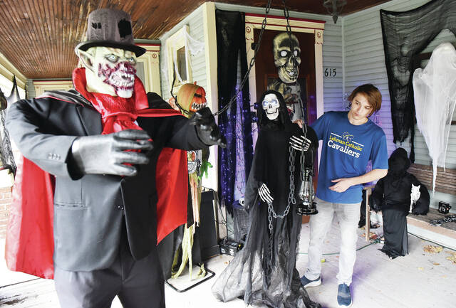 Dominic Casto, of Sidney, puts a skeleton, that keeps falling over, back upright on his porch on Tuesday, Oct. 5. Casto's parents, Kelli and Jason Hart are the decorators of the porch on the house built in 1890 located along South Main Avenue. Kelli and Jason made body molds for their monsters by wrapping themselves in Saran Wrap then several layers of duct tape. They then stuffed the resulting mold with pillow stuffing. The vampire on the left was made with this technique. Kelli said they decided to come back bigger and better than ever this year after not putting up Halloween decorations last year due to the stress of Covid-19 and a family illness.