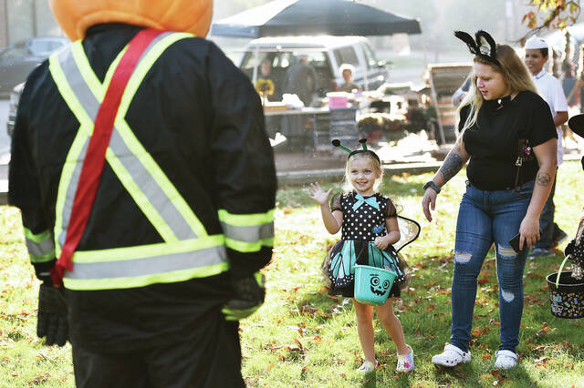 Gracelynn LeMaster, center, 4, of Sidney, waves to Chainer's Field of Screams' Mr. Spooky on the courtsquare. With LeMaster is Alliah Shaver, of Sidney. Gracelynn and Shaver were dressed up for the Downtown Sidney Boos and Brews Festival on Saturday, Oct. 9. Gracelynn is the daughter of Courtney and Jon LeMaster.