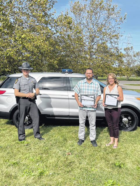 """Ohio State Highway Patrol Lieutenant Joseph A. Gebhart, Piqua Post commander, presents Phillip and Emily Whetstone, of Springfield, with Ohio's """"Saved by the Belt"""" certificates and a license plate bracket on Thursday, Oct. 14, after their safety belt saved them from sustaining life-threatening injuries. The crash involving the Whetstones occurred on Interstate 75 in Shelby County on July 5, 2021."""
