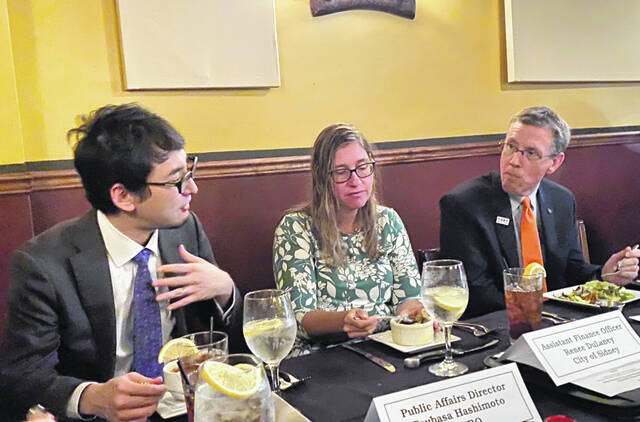 JETRO Public Affairs Director Tsubasa Hashimoto discusses Japan's investment dynamic with Sidney's Finance Officer Renee Dulaney and Troy Safety Service Director Patrick Titterington at the luncheon held last week at The Bridge restaurant.