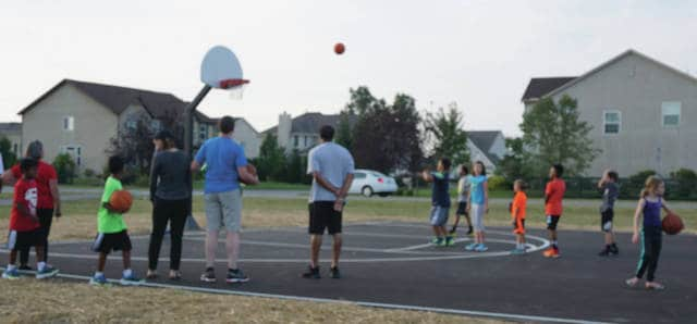 Local children participate in a free throw shooting contest at the new basketball hoops at Center Green Park in Genoa Township.