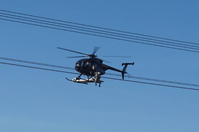 A helicopter hovers next to a power line to let a lineman work do utility work at State Route 3 and Galena Road on Friday morning, Oct. 20.