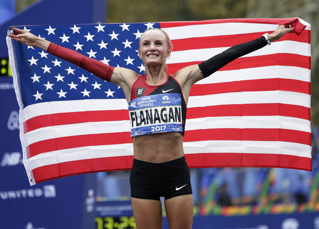Shalane Flanagan of the United States poses for pictures after crossing the finish line first in the women's division of the New York City Marathon in New York, Sunday, Nov. 5, 2017.