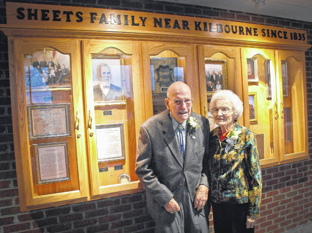 Charles and Betty Sheets stand in front of a display case depicting their family's long legacy in and around Kilbourne since 1835. The display case hangs on the wall of the foyer in the new Brown Township Hall.