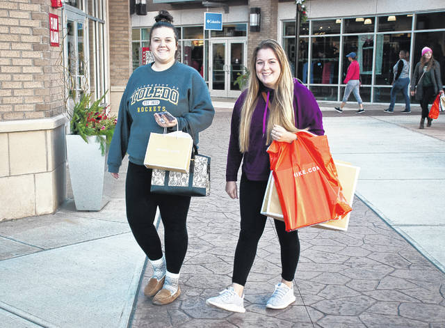 Looking for the deals of the day, Amy Poorman, left, and Madison Myers walk the Tanger Outlet Mall early Black Friday morning. The two said they started Thanksgiving evening, took a break for some sleep, and started back out Friday morning.