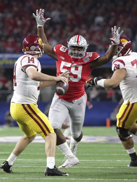 Ohio State defensive lineman Tyquan Lewis (59) closes in on Southern California quarterback Sam Darnold (14) during the first half of the Cotton Bowl NCAA college football game in Arlington, Texas.