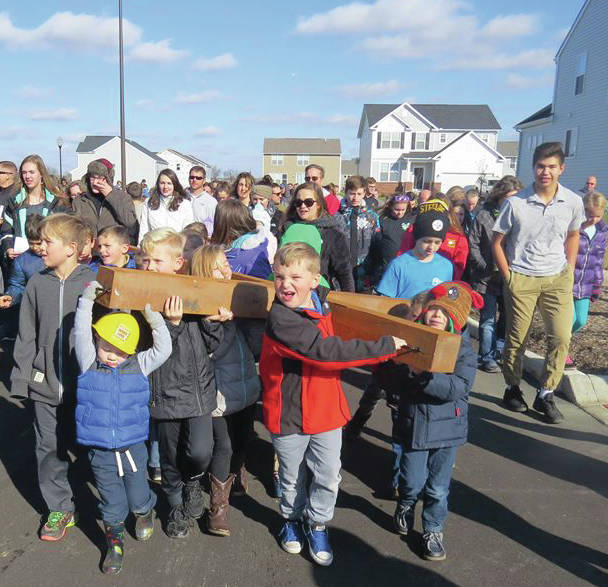 """On Nov. 26, members of Sunbury Christian Church carried a cross 1.8 miles from its old location on Rainbow Avenue to its new location on Admiral Drive. The """"generational journey"""" had children carrying the cross the final steps of the way."""