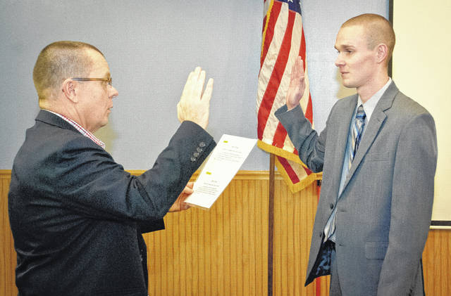 Before Genoa Township's reorganization of the trustee board Thursday, Fire Chief Gary Honeycutt introduced and recommended Ian Fellers to be hired as a full-time firefighter/paramedic with the township's department. Fiscal Officer Patrick Myers, left, swore in Fellers once the motion to hire him as a full-time firefighter for the ship was approved by trustees.
