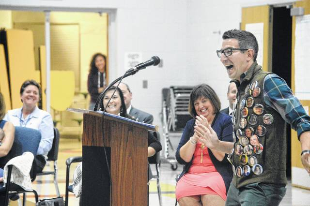Jonathan Juravich, art teacher at Olentangy Liberty Tree Elementary School, talks to his students during a September 2017 assembly after being honored as the 2018 Ohio Teacher of the Year. Juravich showed a vest of buttons with the faces of his colleagues at the school. He makes buttons as prizes for students.