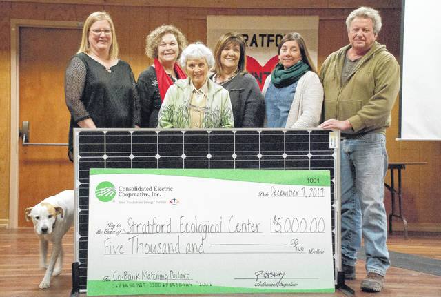 Standing behind one of the solar panels to be installed at the Stratford Ecological Center are, from left to right, Stratford canine Buddy, Consolidated Electric's Hedi Knouff and Vivian Curry, Stratford founder Louise Warner, Consolidated Electric's Pam Hawk, and Stratford's April Hoy and Jeff Dickinson. In front, at the bottom of the solar panel, is a check for $5,000 from Consolidated Electric Cooperative that will be matched by CoBank of Green Village, Colorado.