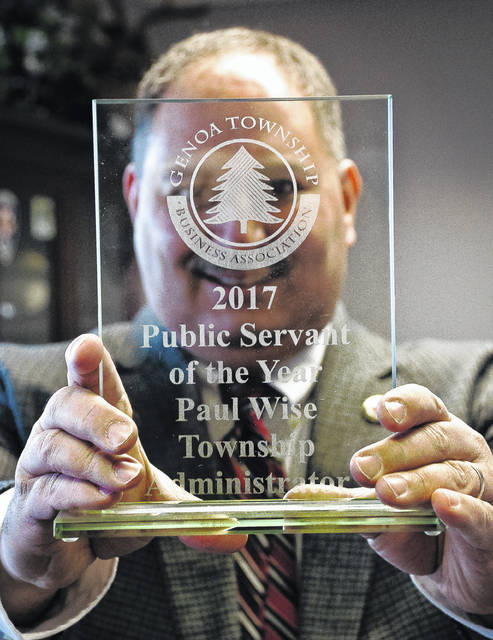 Genoa Township Administrator Paul Wise is the township's 2017 Public Servant of the Year, awarded by the Genoa Township Business Association. Wise is shown hiding behind the award.