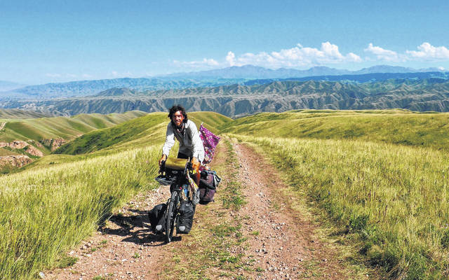 Liberty Township native Luke Miller is pictured riding his bicycle in Kazakhstan.